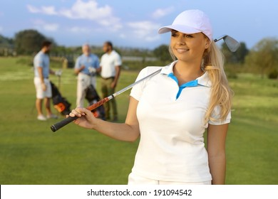 Portrait of pretty blonde female golfer with golf club, smiling, looking away.