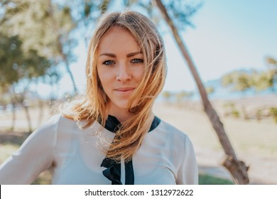 Portrait of a pretty blonde girl, European young woman smiling and looking in the camera in outdoors