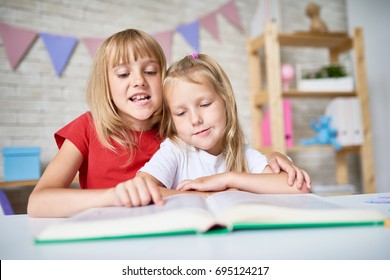Portrait of pretty blonde girl gently embracing her little sister while reading fairy tale aloud, interior of lovely bedroom on background