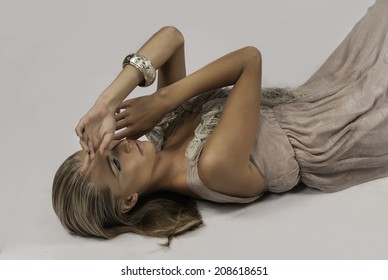 Portrait of pretty blonde woman lying on her back and holding her hands to her face