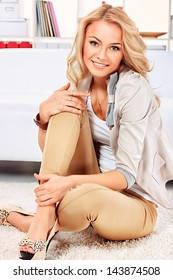 Portrait of a pretty blonde woman sitting on the floor at home.