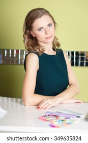 Portrait of pretty blonde young woman near nail bar. Customer in manicure salon