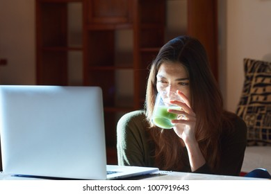 Portrait of pretty brunette girl browsing the Internet via laptop while enjoying glass of fresh green smoothie or juice at home in sunlight.