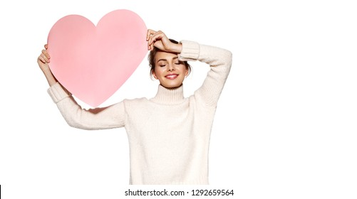 Portrait of pretty brunette girl holding huge pink heart and posing with eyes closed. Beautiful model in trendy outfit. Happiness and love concept. Copy space in right side