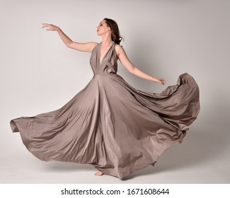 Portrait of a pretty brunette girl wearing a long silver evening gown, full length standing pose against a studio background