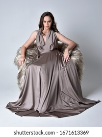 Portrait of a pretty brunette girl wearing a long silver evening gown, full length sitting pose on a chair against a studio background.