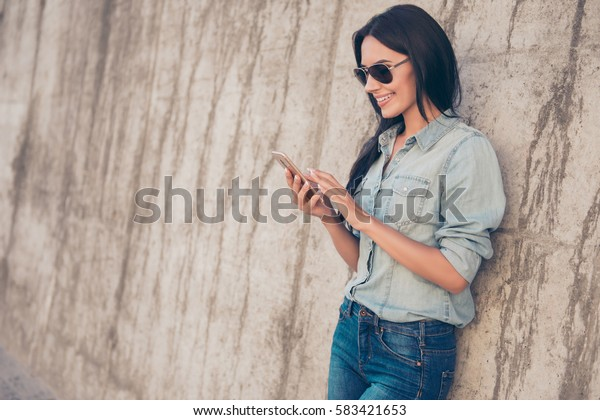 Portrait of pretty brunette read email on her smartphone and  using 4g internet