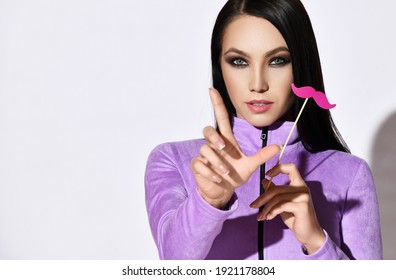 Portrait of pretty brunette woman in purple longsleeve clothes gesturing with finger and holding decorative pink mustache in hand over white background with copy space. Playful mood concept