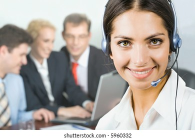 Portrait of pretty business woman with her team on the background