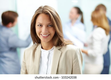 Portrait of pretty business woman looking at camera with working partners on background