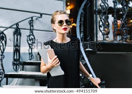 070655d5e1 Portrait pretty businesswoman in black dress on stairs outdoor. She wears  sunglasses