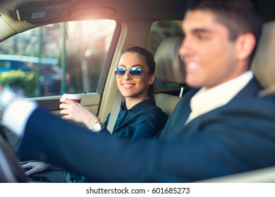 Portrait of a pretty businesswoman and a coworker driving a car