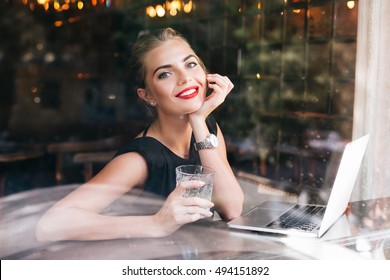 Portrait pretty businesswoman through glass window sitting in cafeteria. She has red lips, holds glass in hand, smiling to camera