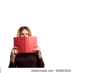 Portrait of a pretty casual girl holding open book at her face isolated over white background