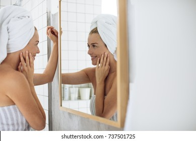 Portrait of pretty Caucasian woman with towels looking in mirror after shower.