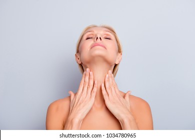 Portrait of pretty, charming, attractive woman enjoying her perfect skin holding two hands on neck, having head up, back with closed eyes, isolated on grey background, moisturizing, hydration concept