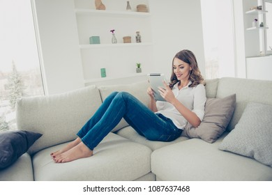 Portrait of pretty, charming, cheerful, trendy house wife in jeans, shirt with curly hair sitting on sofa having tablet in hands chatting with friends checking email searching using wifi internet