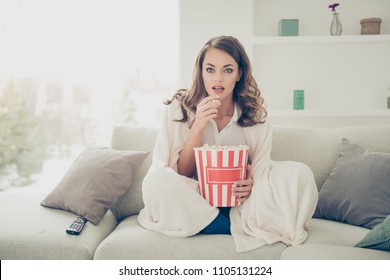 Portrait of pretty, charming, cheerful, trendy house wife with curly hair cover with coverlet having pop corn in hands watching interesting serial having comfort sitting in living room