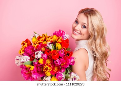 Portrait of pretty charming gorgeous girlfriend, elegant wife, positive mother having big bouquet of colorful aromatic tulips looking at camera isolated on pink background
