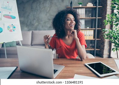 Portrait of pretty cheerful accountant looking away sitting at desk in modern office dreaming about weekend vacation enjoying view from window. Positive thinking person concept