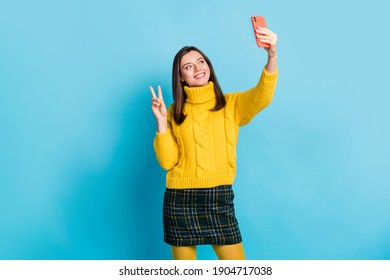 Portrait of pretty cheerful girl blogger taking selfie posing showing v-sign isolated over bright blue color background