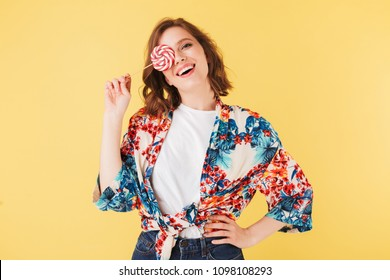 Portrait of pretty cheerful lady in colorful shirt standing and covering her face with lollipop candy while happily looking in camera on over pink background