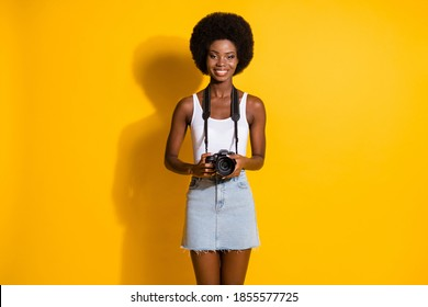 Portrait of pretty cheerful slim wavy-haired girl holding in hands digicam shooting picture isolated over bright yellow color background
