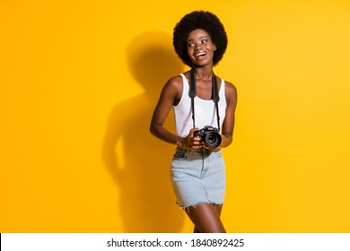Portrait of pretty cheerful thin wavy-haired girl holding in hands digicam enjoying memories isolated over bright yellow color background