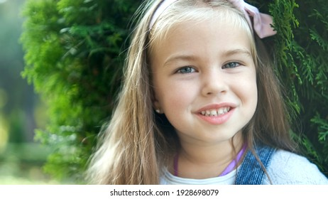 Portrait of pretty child girl standing in summer park looking in camera smiling happily.