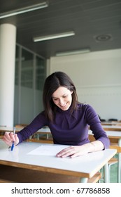 portrait of a pretty college student working in a classroom