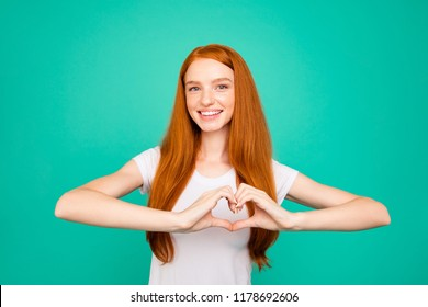 Portrait of pretty, dreamy, attractive, charming, lovely, cute, beautiful, sweet lady make heart shape by hands look and camera, make big white smile isolated on bright turquoise background