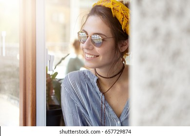 Portrait of pretty European woman in sunglasses and yellow headband looking outside from building enjoying sunny weather. Elegant woman in casual clothes looking out of window. Beauty, leisure cocept