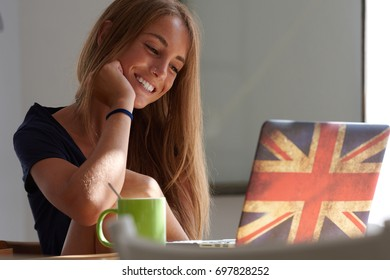 Portrait of pretty fair-haired girl with nose piercing smiling at laptop with British flag on cover.
