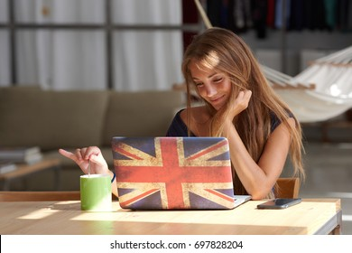 Portrait of pretty fair-haired girl stirring coffee and smiling while using laptop with British flag on cover.