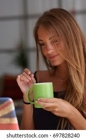 Portrait of pretty fair-haired woman with green mug of coffee enjoying her free time using laptop.