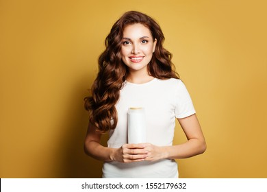 Portrait of pretty fashion model with white cosmetic tube against yellow wall background