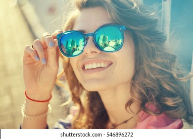 Portrait of pretty fashion woman looking at camera,wears glasses.Woman in glasses,girl with glasses.Shining smile,dental concept