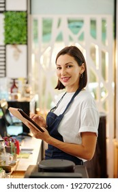Portrait of pretty female barista working on tablet computer and smiling at camera