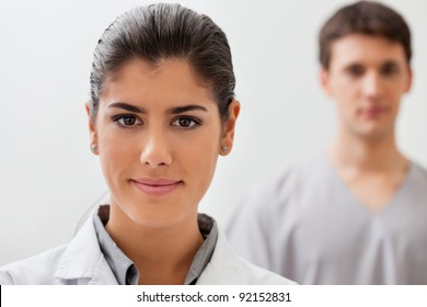 Portrait of pretty female doctor with practitioner standing in background