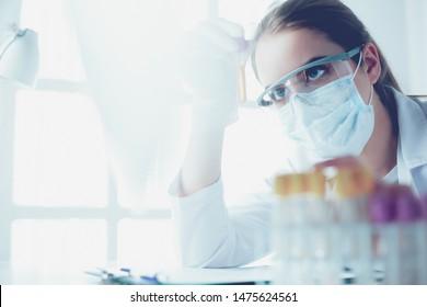 Portrait von hübschen Laborassistenten, die eine Blutprobe im Krankenhaus analysieren