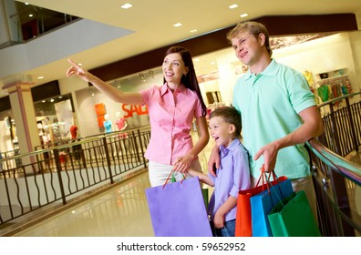 Portrait of pretty female showing something to her husband and son during shopping