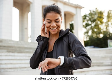 Portrait of a pretty fitness woman in earphones checking her smart watch outdoors