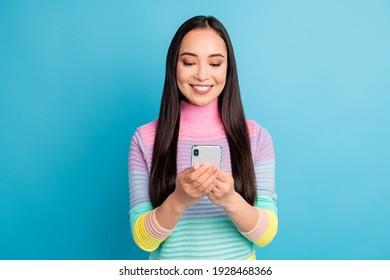 Portrait von ziemlich fokussiertem, fröhlichem Mädchen mit Geräte-Gadget-App einzeln auf hellblauem Hintergrund