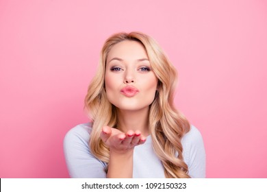 Portrait of pretty friendly girl in casual outfit with modern hairdo blowing air kiss with pout lips palm at camera isolated on pink background. Pomade lipstick concept