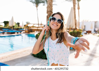 Portrait of pretty girl with amazing smile makes selfie in blue sunglasses and white t-shirt. She listens to music in bright headphones. Background pool with palms. She dances and smiles