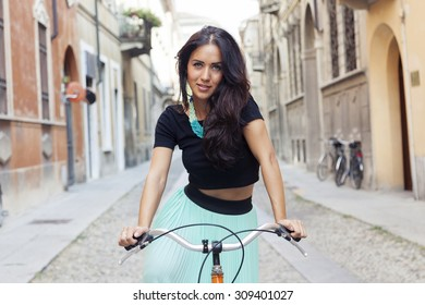 portrait of pretty girl around with the bike in town