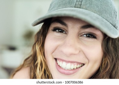 Portrait of pretty girl in baseball cap with long wavy hair smiling at camera happily.