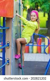 portrait of pretty girl doing rock climbing on playground