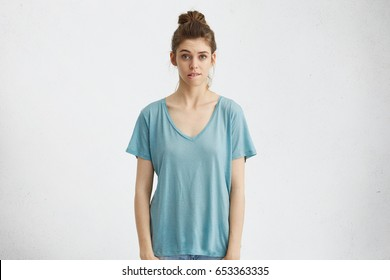 Portrait of pretty girl with hair bun biting lip, looking at camera with regretful or worried expression after she did something wrong. Frustrated young woman having confused indecisive look