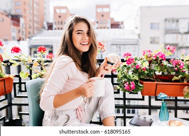 Portrait pretty girl  having breakfast on balcony surround flowers in the sunny morning in city. She holds a cup, croissant, smiling to camera